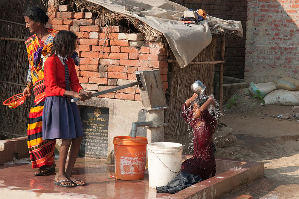 Little girls taking a bath using clean water from Jesus Wells.